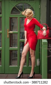 Charming young blonde in red sexy dress posing in front of a green painted door frame. Sensual gorgeous young woman on high heels in red outfit. Portrait of attractive fair hair girl with long legs