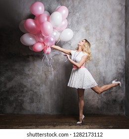 Charming young blonde in a white dress with pink balloons, fly at the party. Happy and cheerful girl with balloons. On gray textured background