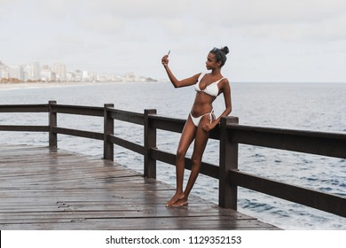 Charming young Brazilian female is posing for the selfie in front of the sea horizon; a svelte cute African-American girl in swimwear is photographing herself on the smartphone near the ocean