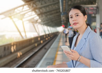 charming young business woman holding smart phone standing on the platform and waiting for the Taiwan high speed rail on a sunny day.