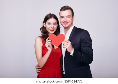 A charming young businessman in a dark suit hugs a delightful young brown-haired woman in a red dress. A couple of lovers hold a red heart in their hand and smile happily, look straight. Copy space.