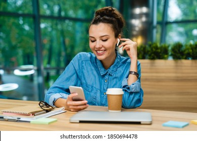 Charming young busy girl checking her phone with earbuds sitting at the desk with laptop and cup of coffee