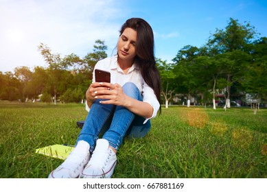 Charming young female chatting on her mobile phone while sitting in park in summer day