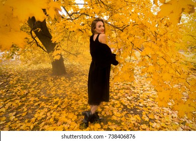 Charming young girl in black coat outdoors in autumn Leaves