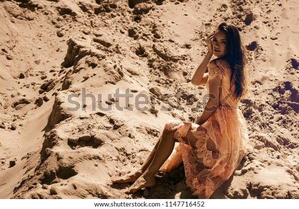 Charming young girl in pinks dress sits on sand and looks at the camera in desert