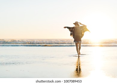 Charming young girl with poncho, hat, sunglasses with beautiful smile walking on the beach at sunset in warm weather. Boohoo style.