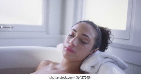 Charming young hispanic woman relaxed in a bathtub.