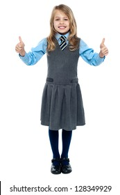 Charming young kid in school uniform showing double thumbs up sign.