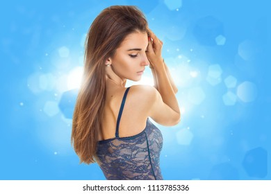 charming young lady in blue lace lingerie with closed eyes in blue studio