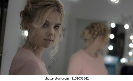 Charming young lady with professional hairstyle and makeup look at camera
