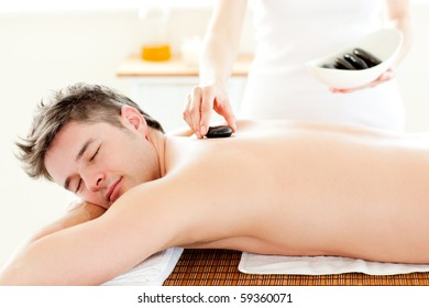 Charming young man receiving hot stone on his back in a spa center