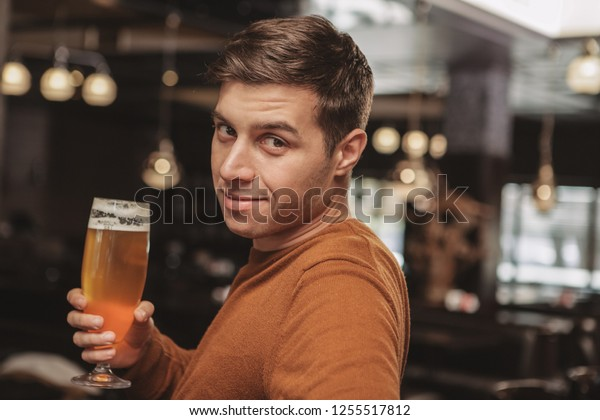 Charming young man smiling to the camera over his shoulder, having glass of cool freshly brewed craft beer at the pub. Attractive male customer relaxing at the restaurant, drinking after work