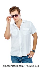 Charming young man in white shirt and blue jeans wearing sunglasses. Isolated on white background.