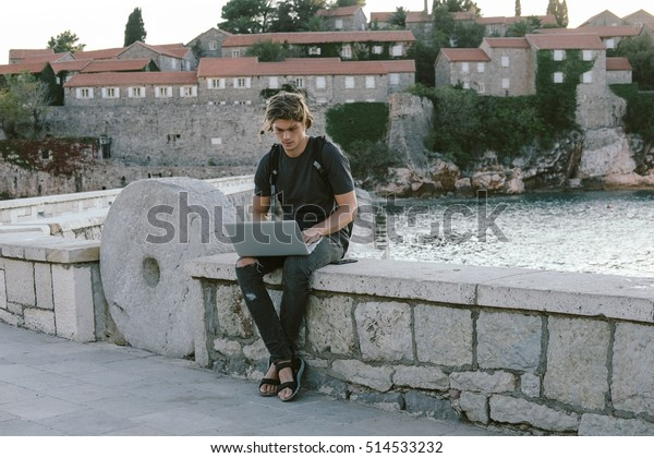 Charming Young man working on laptop near the sea, freelance working, social networks and online shopping concept