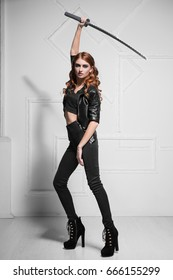 Charming young model in black clothes posing with steel sword