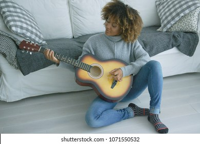 Charming young model in cozy sweater sitting on floor of living room and playing guitar alone looking inspired.