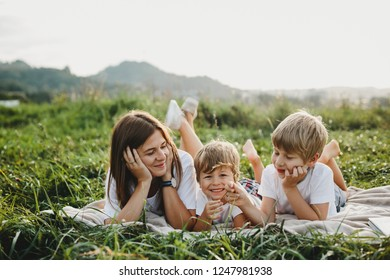 Charming young mother has fun with her little sons lying on a plaid on green grass