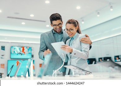 Charming young multicultural couple in formal wear trying out new tablet in tech store.