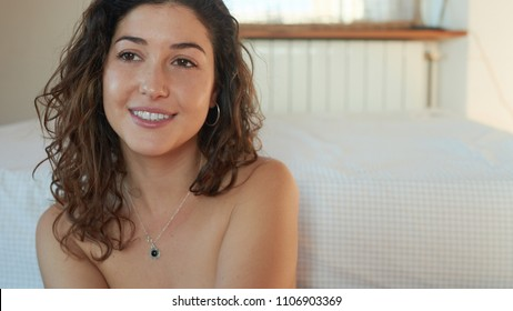 Charming young nude girl with curls sitting on floor near bed and looking away in dreams