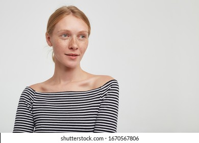 Charming young pretty redhead lady with natural makeup looking thoughtfully aside with gentle smile, dressed in striped top while standing over white background