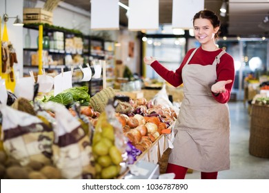 Charming young seller posing with counter of golden onion in grocery