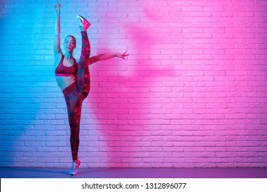 Charming young slim gymnast woman in sports clothing stretching in front of brick wall in neon lights. Flexible muscular woman doing gymnastic split.
