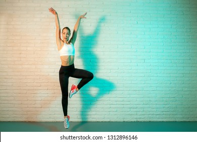Charming young slim gymnast woman in sports clothing stretching in front of brick wall in neon lights. Flexible muscular woman doing gymnastic exercises.
