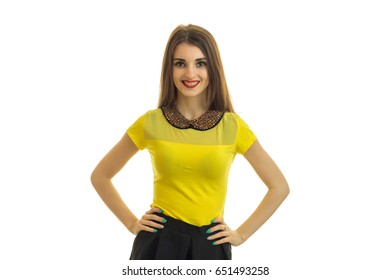 a charming young smiling girl holding hands on the sides and faces the camera in bright blouse