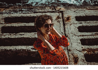 Charming young smiling woman in red dress with short curly hair looking at camera. Female retro sun protection sunglasses. Enjoy summer vacation concept. Close up portrait girl. Travel to Ukraine