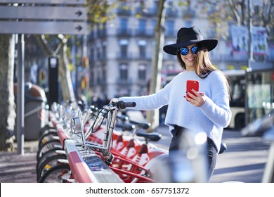 Charming young traveler in stylish hat and sunglasses making payment online transfer money for service renting bicycle outdoors for having city tour using modern smartphone connected to 4G internet