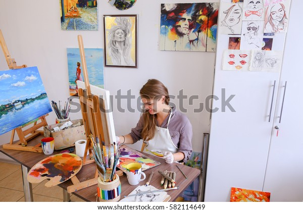 Charming Young Woman Artist Draws Oil Painting With Purple Flowers on a White Canvas, Female Enjoying Favorite Work, Hobbies, posing  for camera and Painting Picture to Order or Gift. Woman With Lon