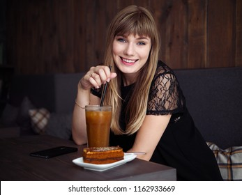 Charming young woman with beautiful smile enjoying orange juice frappe in cozy coffee shop relaxing during free time