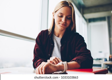 Charming young woman with blonde hair looking at wristwatch to tracking time sitting at desktop in stylish loft.Beautiful student dresssed in casual outfit managing clock on smartwatch in coworking
