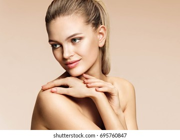 Charming young woman with blonde hair. Photo of beautiful woman with healthy skin on beige background. Youth and skin care concept