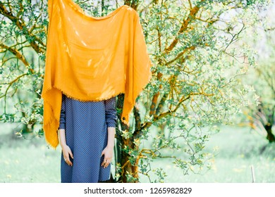 Charming young woman in blue dress having fun with bright yellow stole in nature on a warm Sunny day. slender lady threw her handkerchief on tree branch and hid behind it. Carefree student on walk