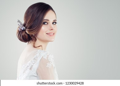 Charming young woman bride with makeup and bridal hairstyle. Pretty woman fiancee on white background with copy space, face closeup