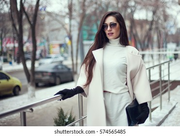 Charming young woman in coat with long brunette hair wearing a hat enjoying snowfall in big city. Cheerful emotions, smiling,  positive face emotions, winter weather. Leather gloves and stylish purse.