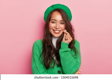 Charming young woman with dark long hair makes korean love sign, shapes heart with fingers, wears bright fashionable green beret and jumper on buttons, isolated over pink background. Hand gesture