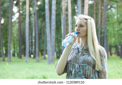 Charming young woman drinking water walking in a summer park