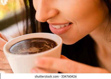 Charming young woman enjoying aroma coffee in cafe
