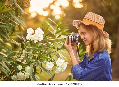 Charming young woman enjoying her time outside in park with sunset in background. Taking photos of flowers.