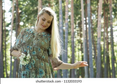 Charming young woman enjoying pregnancy time, outdoors portrait
