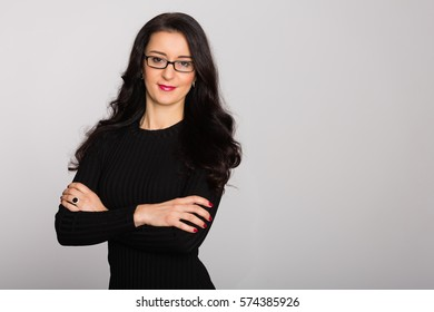 Charming young woman in glasses stands on a background of gray wall. Age 32 years.