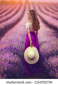 A charming Young woman with a hat in a purple skirt walks around the lavender field at sunset.