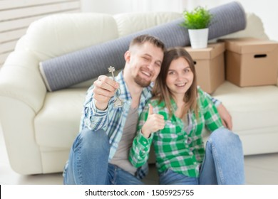 Charming young woman and her husband holding in hands the keys to their new apartment while sitting in her new living room. Housewarming and mortgage in new building concept
