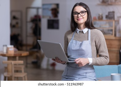 Charming young woman holding laptop and smiling.