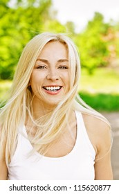 Charming young woman laughs merrily dressed in white, against green of summer park.
