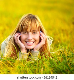 Charming young woman lies on summer lawn and smiles.