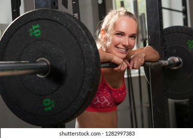 Charming young woman looking at the camera and resting after workout with barbell. Fitness, sports. Concept of Strong Woman
