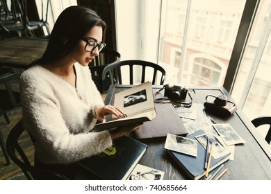 Charming young woman looks at old photoalbums sitting in a cafe